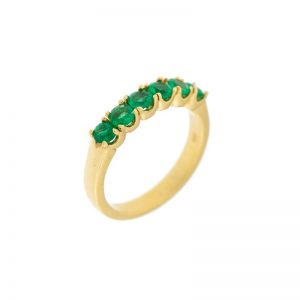 gold wedding band with six round emeralds