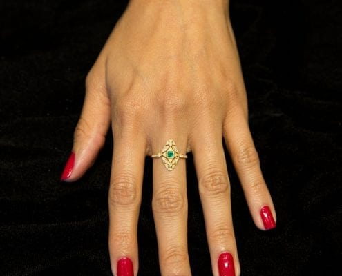 emerald and diamond fashion ring in yellow gold on hand model