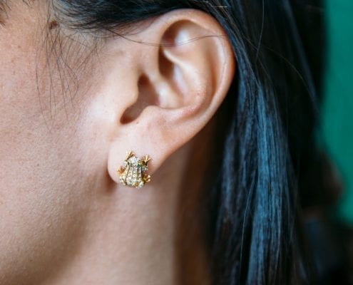 emerald and diamond frog earrings in yellow gold on model ear