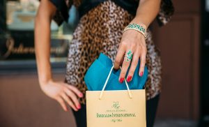 Photo of a female with an emerald ring and bracelet holding an emeralds international shopping bag.